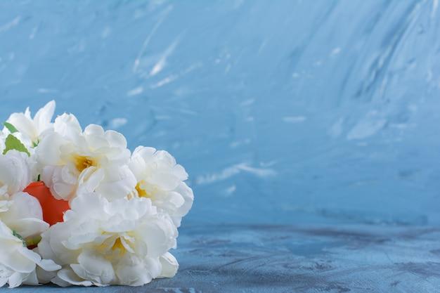 Mazzo di fiori pallidi in un vaso arancione su blu.