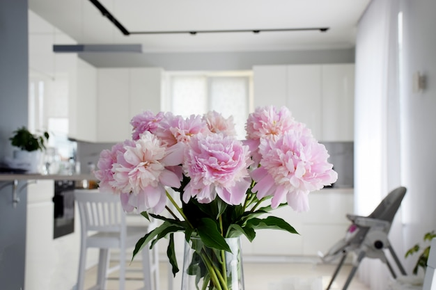 Bouquet of pastel pink peony flowers in bloom with white kitchen on background