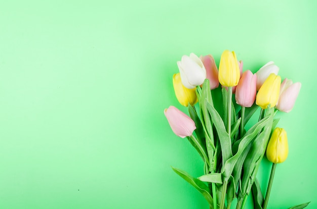 Bouquet of pastel tulips on green table.