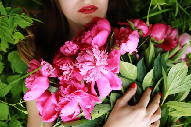 Bouquet of peony. beautiful young woman lies among peonies. holidays and events. valentine's day. spring blossom.