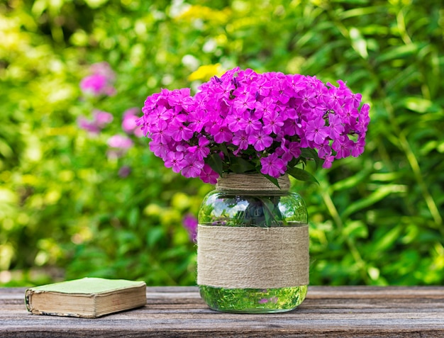 Bouquet of phlox flowers in a glass vase and an old book on the table on nature background, selective focus