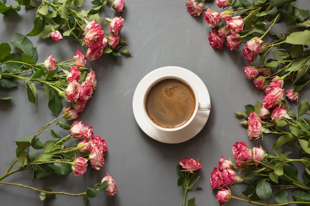 Bouquet of pink bush roses and cup of coffee