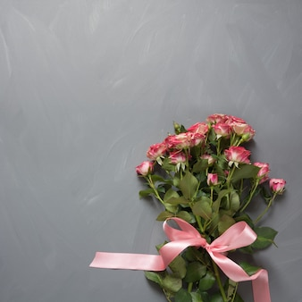 Bouquet of pink bush roses with pink bow on vintage gray.