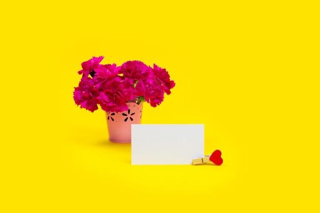 黄色の背景にカードと花束ピンクのカーネーションの花。