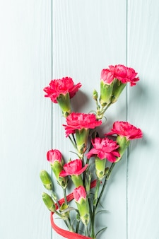 Bouquet of pink carnation on light turquoise wooden background