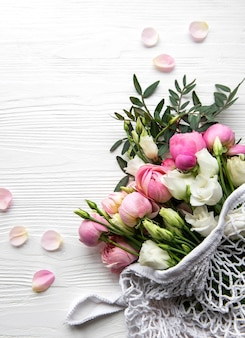 Bouquet of pink colored roses in string shopping bag. top view, flat lay.
