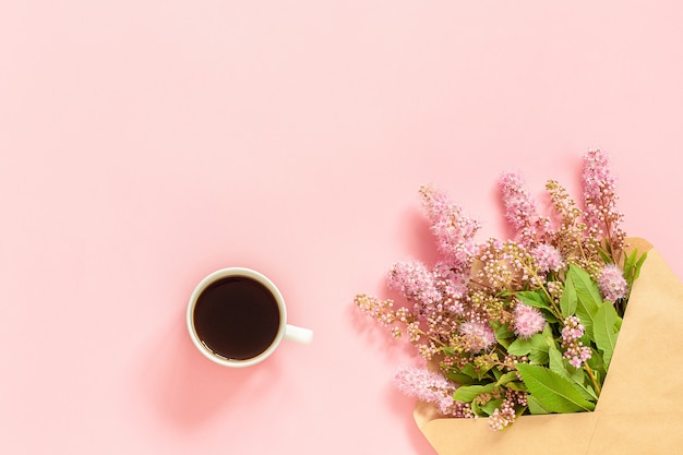 Bouquet of pink flowers in envelope, cup of coffee and a white blank card for text on pink background