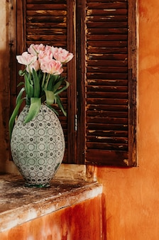 Bouquet of pink flowers in an old big vase on a window sill