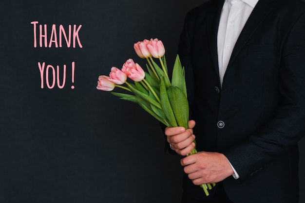 Bouquet of pink flowers of tulips in men's hands. greeting card with the inscription thank you