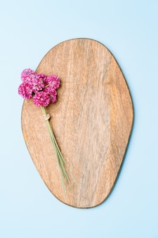 Bouquet of pink flowers on wooden board on pink background, copy space.