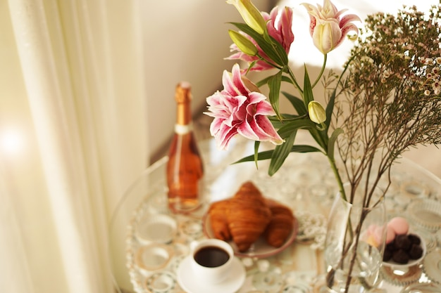 Bouquet of pink lilies. cup of coffee, croissants and a bottle of wine on a blurred background. festive breakfast. light positive photo