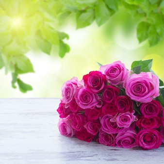Bouquet of pink and magenta fresh roses on table in garden Premium Photo