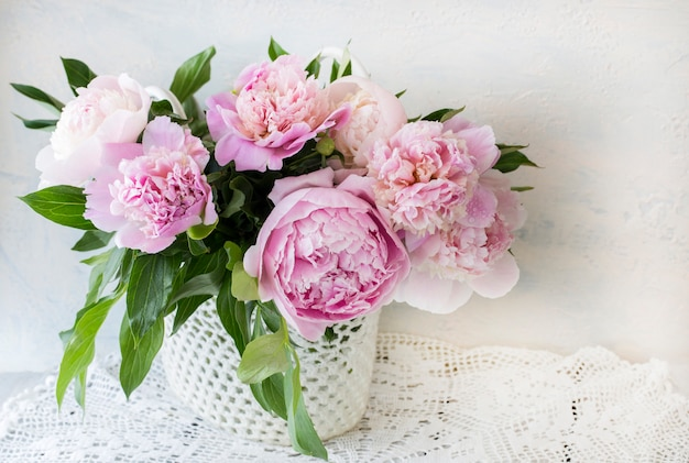 Bouquet of pink peonies on a wooden table in a handmade basket on lace tablecloth