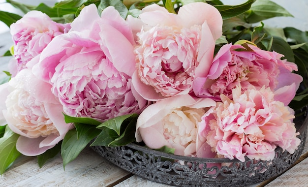 A bouquet of pink peonies on a wooden table in an old vase