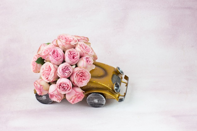 Bouquet of pink roses in the car on a pink background