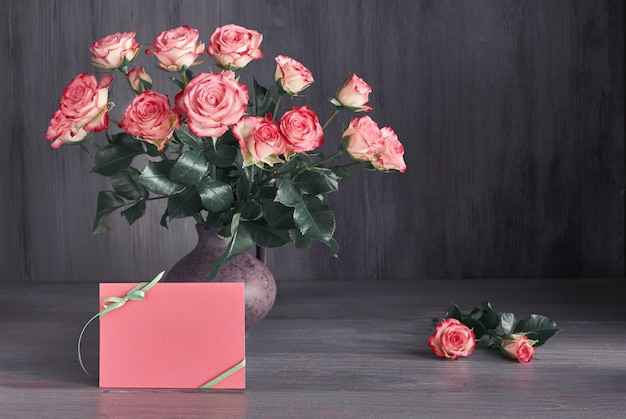 Bouquet of pink roses on dark rustic background with copy-space on blank paper card