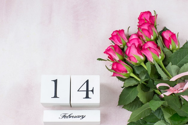 Bouquet of pink roses and the date of february 14 on cubes