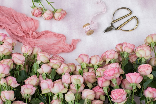 Bouquet of pink roses, scissors, lace ribbon