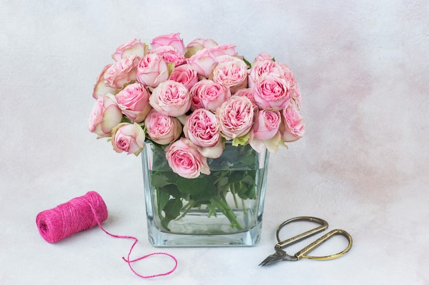 Bouquet of pink roses in a vase, ribbon and scissors