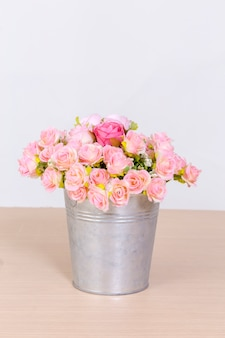 Bouquet of pink roses in vintage pot on wooden background