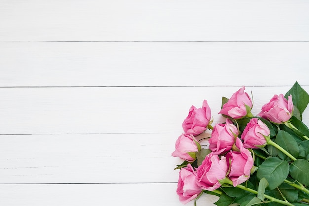 Bouquet of pink roses on white wooden background. top view, copy space.