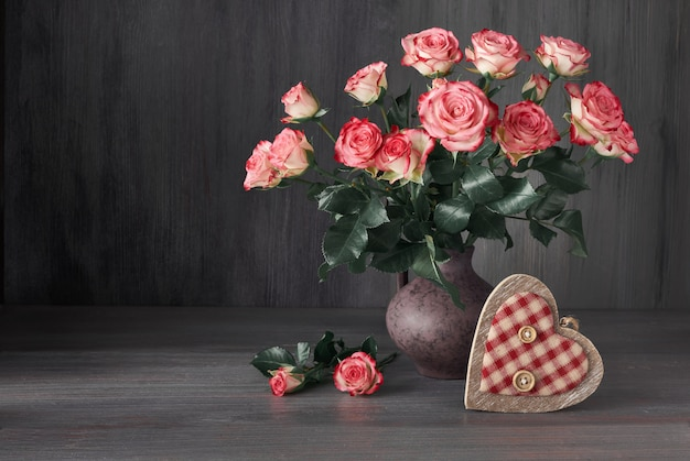 Bouquet of pink roses with decorative wooden heart on dark rustic wood