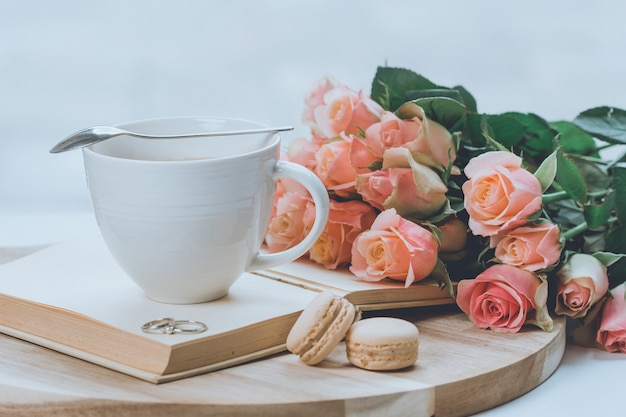 Bouquet of pink roses on a wooden board with a glass on top of the book and macaroon cookies