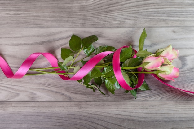 Bouquet of pink roses wrapped in ribbon on wood