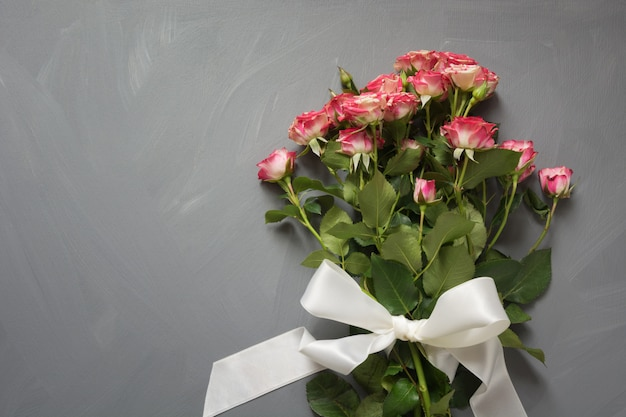 Bouquet of pink spotted bush roses with white ribbon on gray