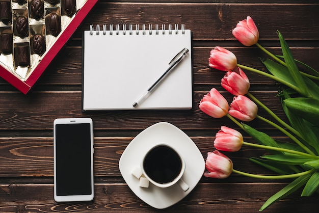 Bouquet of pink tulip flowers with a cup of coffee and a box of chocolates and an empty notebook with a smartphone