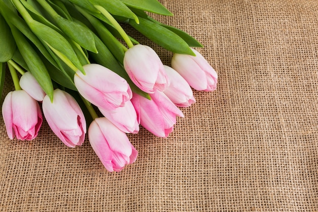 Bouquet of pink tulips on burlap background. copy space