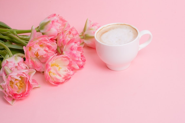 Bouquet of pink tulips  a cup of coffee on a pink background