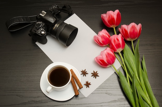 Bouquet of pink tulips, dslr camera, cup of coffee, cinnamon, star anise and sheet of paper