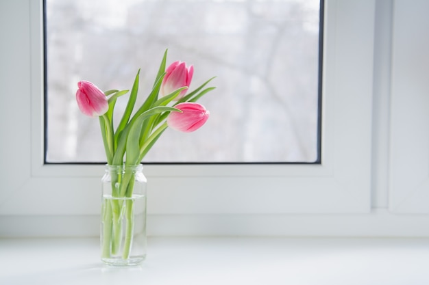 A bouquet of pink tulips in a glass jar is on the windowsill in the house.