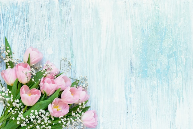 Bouquet of pink tulips and gypsophila flowers on blue wooden background. top view, copy space