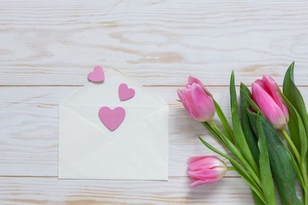 Bouquet of pink tulips and hearts pattern in paper envelope