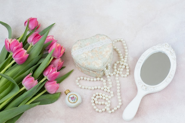 Bouquet of pink tulips, mirror, perfume bottle, casket and pearl beads