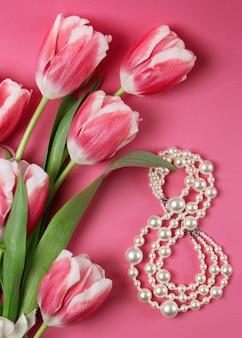 Букет розовых тюльпанов на розовом столе.