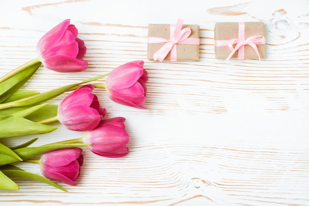 Bouquet of pink tulips and packaged gifts on a white wood, top view