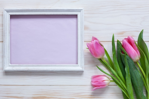 Bouquet of pink tulips and place for text in wooden white frame
