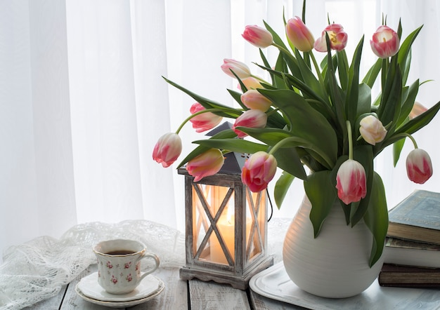A bouquet of pink tulips in a vase, books, a candle and a cup of coffee