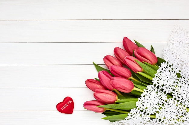 Bouquet of pink tulips on white wooden background.
