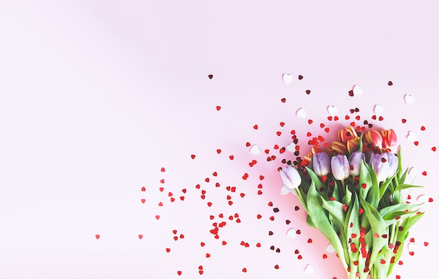 Bouquet of pink tulips with decorative heart sprinkles on soft pastel light background. top view. valentines day festive background.
