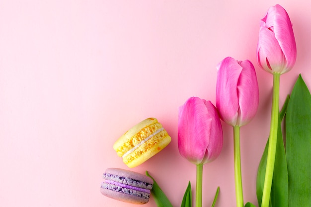Bouquet of pink tulips with macaroons. tulips in a waffle glass of ice cream. spring composition. spring concept. tulips in a vase with sweets.