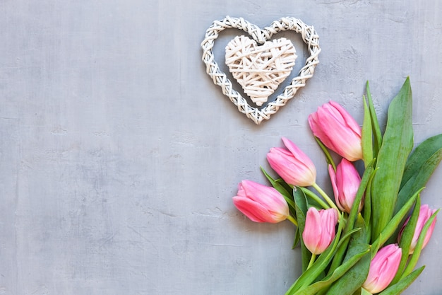 Bouquet  of pink tulips and wooden hearts pattern