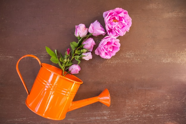 Bouquet of pink white roses in a vase, watering can and a cup of coffee on a wooden table.