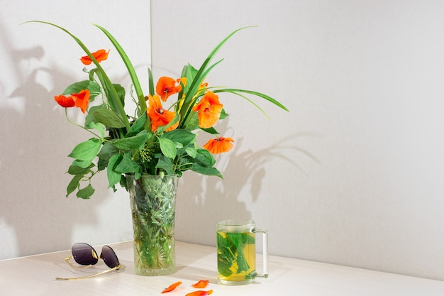 A bouquet of poppies in a glass vase on the table in the room. nearby is a mint of mint tea and sunglasses. interior corner with copy space.