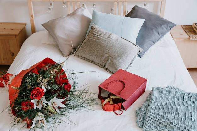 Bouquet and presents on bed