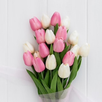 Bouquet of pretty pink and white tulips on wooden background