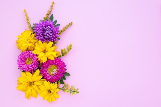 Bouquet of purple asters and yellow daisies on a pink paper background, mockup with copy space